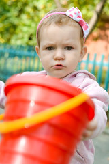 A serious, frowny little girl not giving her toys on a playground. Ability to share your own toys with other children. Behavior of the child in the kindergarten. Communication problems. Ownership.