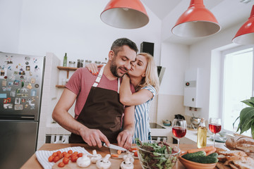 Charming blond lady kissing husband while he cooking dinner