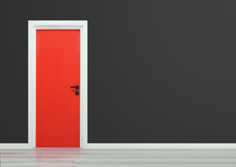 Red door with black handle in a dark grey wall