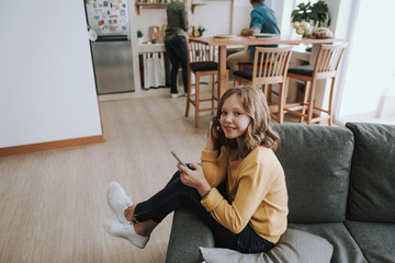 Cute little girl sitting on couch and using cellphone at home