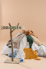 wooden sign with go green lettering near pile of clothing on beige background, environmental saving concept