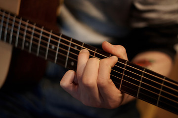 A person performs a melody on an acoustic guitar, holding a hand chord on the fretboard