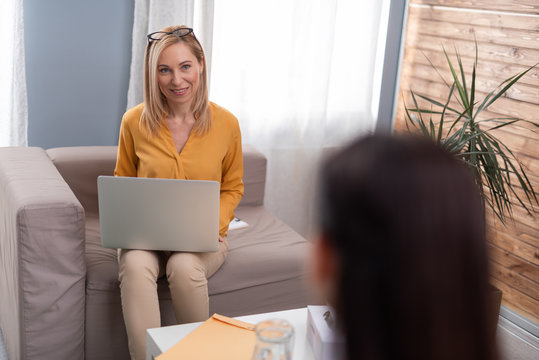 Psychologist talking to brunette female patient in consulting room