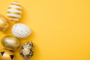 Easter golden decorated eggs on yellow background. Minimal easter concept. Happy Easter card with copy space for text.