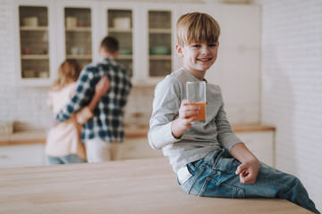 Positive boy holding his glass of juice and smiling