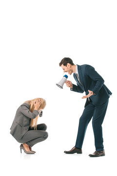 angry male boss yelling into megaphone at stressed female employee isolated on white