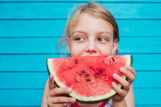 Little girl eating a ripe juicy watermelon over blue plank wall background