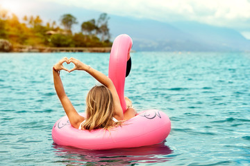 Blond woman loving her flamingo toy in sea