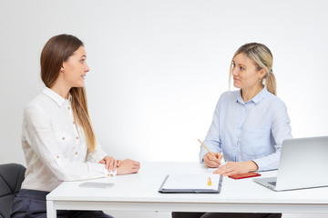 Beautiful blonde caucasian female boss in a blue shirt interviews new cute brunette female employee sits by the desk in the office with the white background.