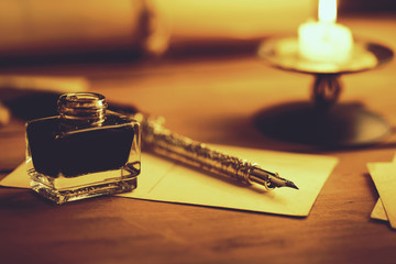 vintage quill pen and inkwell on wooden table in candlelight