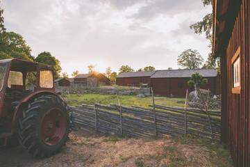 historisches, typisch schwedisches Dorf mit Holzhäusern, Zäunen und Traktor