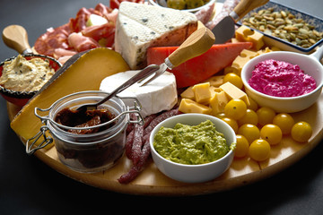 Antipasti board with various cheese and meat snacks with hummus and olives on wooden board