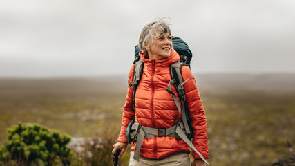 Senior woman on a hiking adventure Wall mural