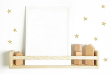 The blank poster on the wooden shelf with star-shaped stickers on the wall