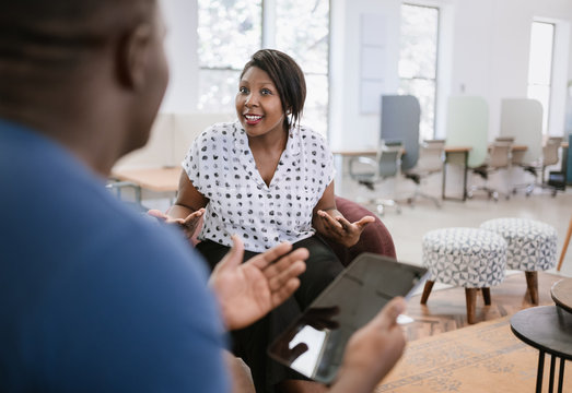Beautiful black african business woman sitting talking to a man during a meeting, both using expressive hand gestures and the man is holding a digital tablet.In a modern co working office