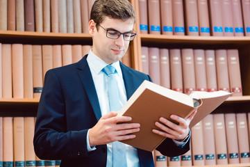 Rechtsanwalt in seiner Kanzlei liest in dicken Büchern und denkt nach