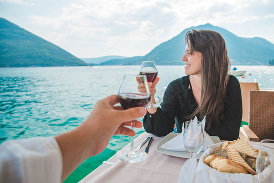 woman with man drinking wine in restaurant at seaside with beautiful view of bay and mountains