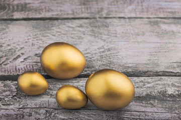 Background of Golden eggs on a wooden surface