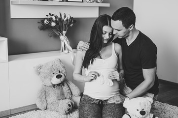 Image of husband holding belly of pregnant wife, socks for baby in hands. Pregnant woman or girl and man hugging tummy at home. Loving Couple. Parenthood concept. Baby Shower. Black and white photo.