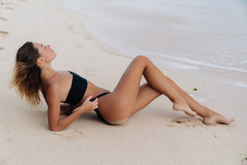 Tanned girl in black swimsuit lying on white sand beach. Female model with sexy body enjoys relaxing near ocean