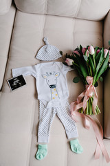 Set of baby clothes in white color. Newborn accessories: socks, cap, ultrasound scan or picture of boy. Bouquet flowers greetings for a party in honor of pregnant at home. Top rear view. baby shower.