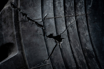 Old cracked rubber tire texture. Abstract damaged black surface background. Tire tread problem and solution concept