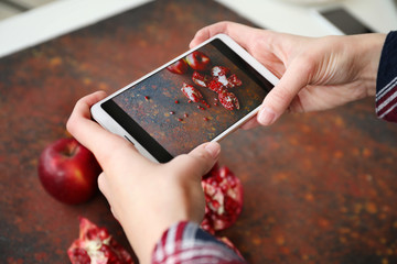 Female food photographer with mobile phone taking picture of fresh fruits, closeup