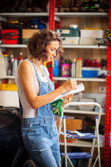 Woman car mechanic in blue overalls reading instructions in garage