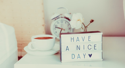 Have a nice day message on lighted box, alarm clock, cup of coffee and flower on the bedside table in sun light. Good morning mood. Hospitality, care concept. Vintage tonning. Wide banner. Copy space.