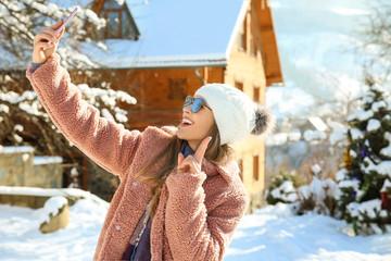Beautiful woman taking selfie at snowy resort