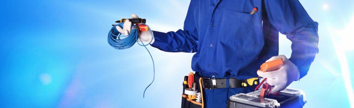 Electrician with tools and electrical equipment isolated with lights