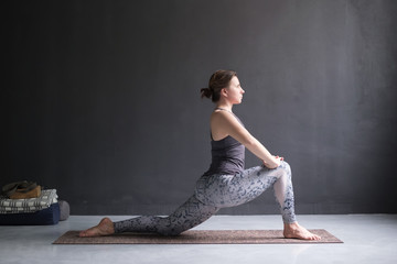 Woman doing Hatha yoga asana Anjaneyasana or low crescent lunge pose isolated,