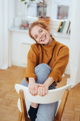 Pretty girl with friendly smile sitting on chair