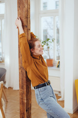 Happy young woman stretching with a blissful smile