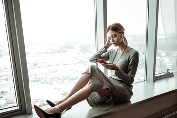 Woman sitting on window sill while reading newsfeed on smartphone