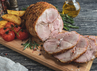 Wall Mural - Roasted pork roulade sliced, roll with potato and tomato on cutting board