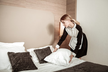 Professional housekeeper putting clean white pillow on bed