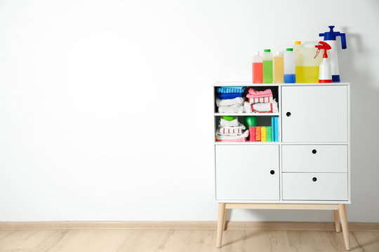 Cabinet with different cleaning supplies near white wall. Space for text