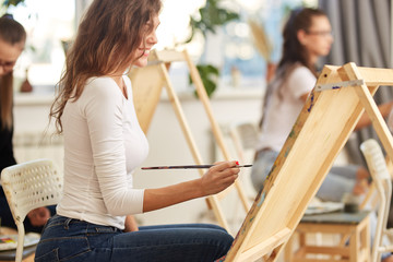 Smiling girl with brown curly hair dressed in white blouse paints a picture at the easel in the drawing school