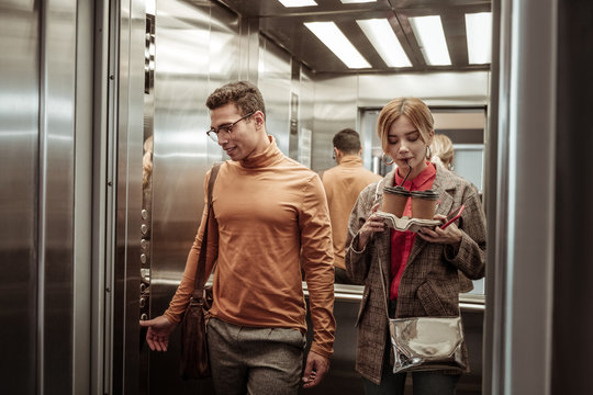 Wife sipping cappuccino while taking elevator with her man
