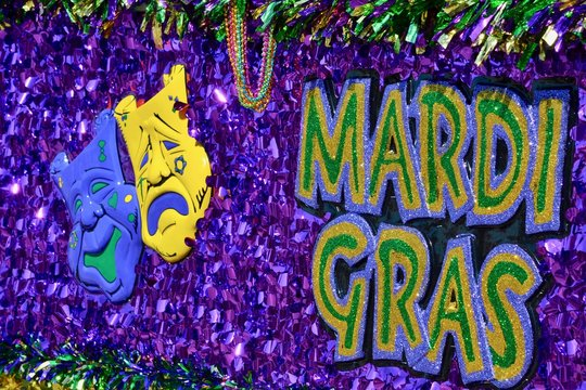 Mardi Gras masks and sign on float in parade