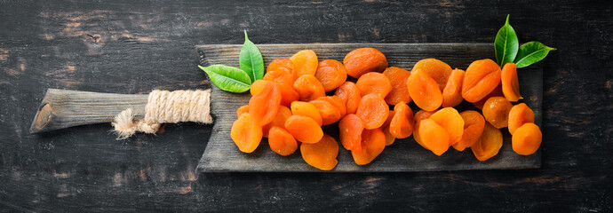 Dried apricots on a black background. Dried fruit Top view. Free space for your text.