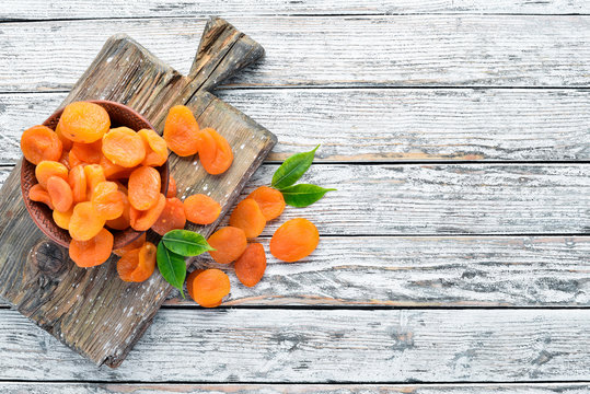 Dried apricots on a white wooden background. Dried fruit Top view. Free space for your text.