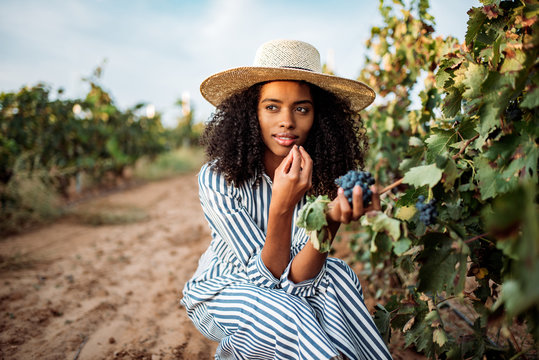 Young black woman eating a grape in a vineyard