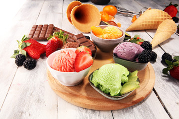 Set of ice cream scoops of different colors and flavours with berries, chocolate and fruits.