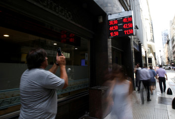 A man takes a picture of an electronic board showing currency exchange rates in Buenos Aires' financial district