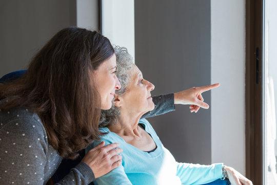 Adult daughter visiting elderly mother