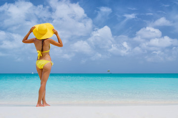 Beach vacation travel bikini woman in Caribbean. Lady with slim sexy body standing on tropical white sand beach in Caribbean wearing yellow sunhat looking at perfect turquoise sea. Luxury destination