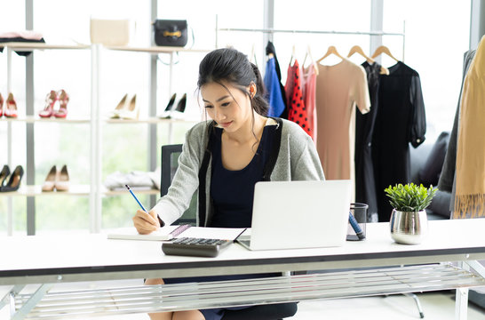 Beautiful young Asian woman working checking figures and stock on her notebook in clothes shop. Startup Small Business Owner Concept.