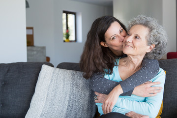 Pretty woman kissing senior mother and hugging her from back